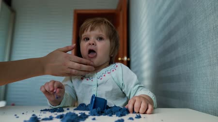 kinetik : Little cute baby girl licks her hands, soiled by kinetic sand on the background of beautiful blue wallpaper in slow motion. Loving mom wipes her daughters dirty mouth