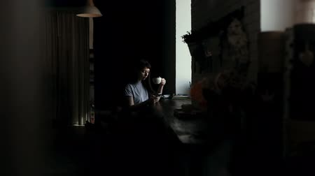schrikken : Girl sits by window, drinks coffee from a cup and typing message on phone in slow motion. Camera moves horizontally. Someone is spying on young woman who drinks sitting at table in cafe and texting