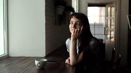 saçlı : Girl with a cup of coffee is sitting in a cafe, smiling and looking out the window in slow motion. Young beautiful woman with a small ring in her nose, thinks and smiling, tapping herself on face