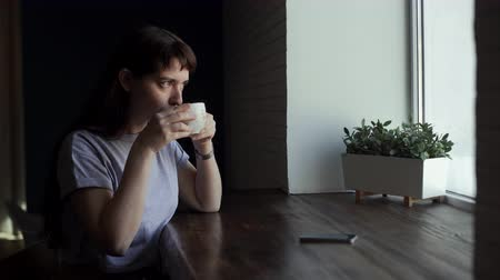 saçlı : Young pretty girl drinking coffee in a cafe near a window. Beautiful woman resting alone over a cup of tea in a cafe. Brunette girls waiting for somebody in the cafe. On the table is a phone Stok Video