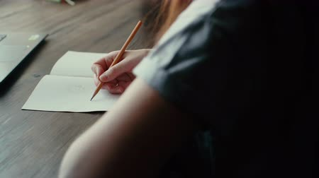 grafit : Girl sits in cafe and draws in notebook with pencil close up. Girls face is not visible. Camera shoots from behind the shoulders of young woman. On the table next to the girl are her phone and laptop