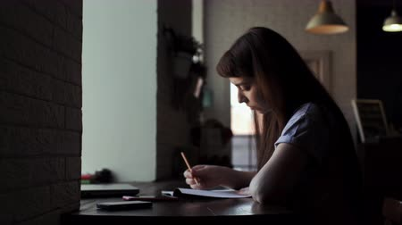grafit : Young cute female artist sits at the desk and draws in a notebook. Novice writer makes sketches in his notebook. Next to the beautiful serious girl on the black table there are her phones and laptop Stok Video