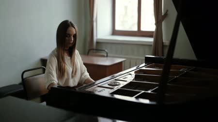 dizgi : Young woman pianist playing gentle classical music on grand piano near the window. Talented girl pianist with long straight hair masterfully plays on the piano. Girl wears choker around her neck Stok Video
