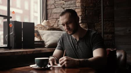 karizmatikus : Brutal man with stubble on his face and a tattoo on his arms is sitting in a cafe at a table with a dark cup of coffee or tea and making entries in his diary against the window.