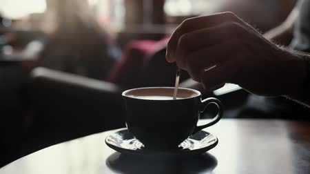 smetanový : Close up man hand stirring coffee with milk using a spoon. Against the backdrop of cafe and vanity everyday life. In the background a blurred silhouette of a girl