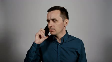 входящий : Closeup portrait of a young business man talks on the phone and asks his companion to wait next to him in front of a camera on a white background. Charismatic actor play concept of emotions Стоковые видеозаписи