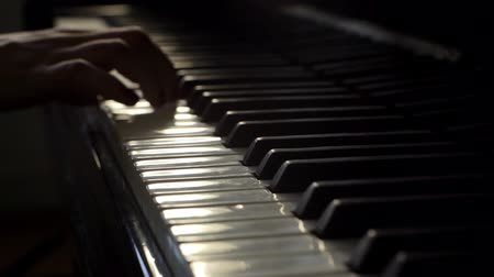piyano : Woman pianist plays gentle classical music on a beautiful grand piano with one hand close-up in slow motion. Piano keys close up in dark colors. Student trains to play the piano Stok Video