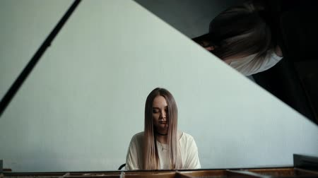 dizgi : Girl pianist with long hair plays gentle classical music on a grand piano on the background of a beautiful wall in slow motion. Student pianist preparing for classes in the classroom Stok Video