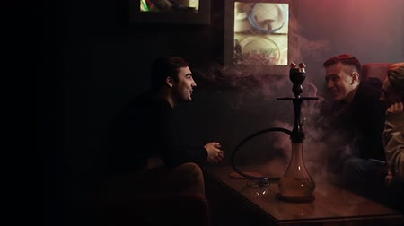 despedida de solteros : Three young cheerful friends smoke in a hookah at dark room of shisha lounge in slow motion. Group of friends of students carefree spend their free time in the hookah room. Camera moves horizontally. Archivo de Video