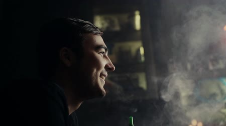 inhaling : Close-up handsome guy smokes hookah and has fun with his friendsat dark room of shisha lounge in slow motion. Young hipster man smoking a hookah and exhales with a smile through his mouth