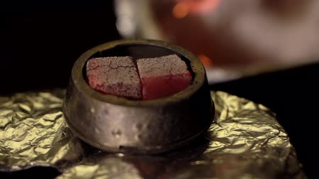 csipesz : Close-up preparation of a bowl for a hookah in slow motion. Kindling coals for hookah in hookah bar. Closeup an hand holds red-hot coal with tongs. Modern hookah with coconut charcoal and shisha smoke Stock mozgókép