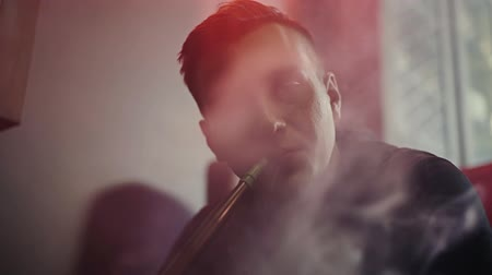 tabaco : Close-up attractive guy with the fashionable hairstyle smoking hookah and exhales smoke through his mouth smoke on camera at dark room of shisha lounge in slow motion. Young man relaxing with friends