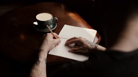 charisma : Mans tattooed hand writes in a notebook on a coffee table in a dark cafe close-up. Shooting from the back. Nearby is an empty coffee cup. Left-handed guy makes notes on paper. Stock Footage