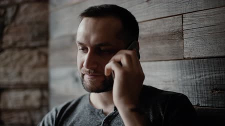 харизматический : Close-up of brutal man with bristle and tattooed hands sits at a table in a cafe and speak by phone on the background of a beautiful wooden plank wall.