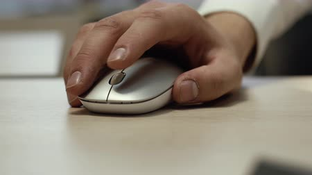 fare : Close-up of a man hand uses white wireless mouse. Closeup male hand scrolling the wheel of a light wireless mouse. Guy arm clicks on the stylish wireless mouse buttons close up. Camera falls down. Stok Video