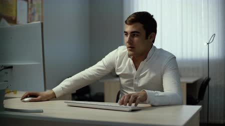 escritórios : Serious focused businessman works on desktop. Handsome man using computer sitting at the office desk. Busy developer programmer concentrated on coding. Trader looking at screen monitoring stock online Stock Footage