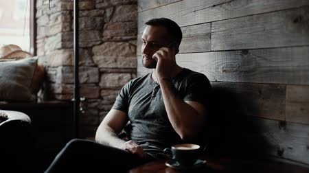 sörte : Charismatic man with bristles and tattooed hands is sitting at a table in a cafe and talking on the phone near the window against the background of a wooden plank wall. On the table is a cup of coffee