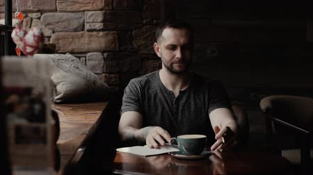 taş duvar : Manly man with stubble and with tattooed arms sitting by the window with tattooed arms in cafe takes notes in notepad and is thinking about something. Left-handed knocks a cup of coffee with a pencil Stok Video