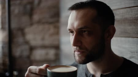 charisma : Close-up portrait of  manly man with bristle and tattooed hands siting at a table in a cafe, picks up a cup of coffee from a table and drinks against the background of a beautiful wooden plank wall