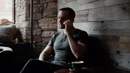 charisma : Brutal man with bristles and tattooed hands sits at a table in a cafe, takes the call and starts talking on phone near window against background of a wall with stone masonry. On table is cup of coffee Stock Footage