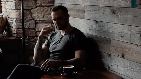 charisma : Brutal man with stubble and tattooed arms is sitting at a table in a cafe and thinking about something. Someone is calling the guy phone. Man takes call and starts talking. On table is cup of coffee