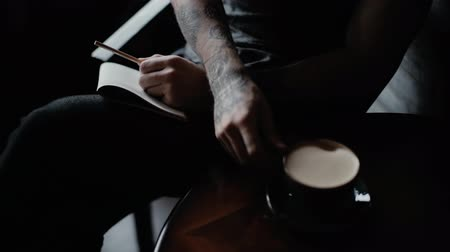 charisma : Man with tattooed arms writes in his notebook, takes a cup of coffee and drinks close-up in the interior of the cafe. Handsome guy picks up a cup of coffee from a table and drinks Stock Footage