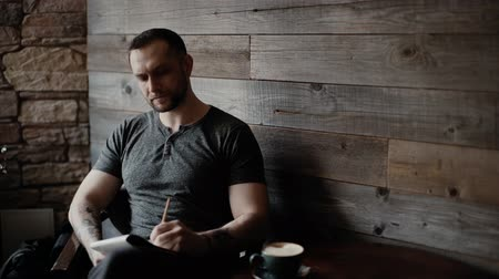 important : Brutal man with bristles and tattooed hands sits at a table in a cafe and takes notes in his notebook on the background of a beautiful wooden plank wall. Left-handed guy makes notes on paper