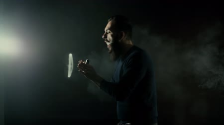 vaper : Bearded man showing vaping tricks and making vapor jellyfish with electronic cigarette on black background in slow motion. Light rays from a lighting fixture in a professional dark studio.