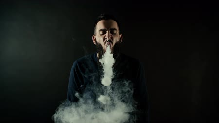 vaper : Portrait of bearded brutal man showing vaping tricks and making many small ring circles of steam with electronic cigarette on black isolated background in slow motion in professional dark studio.