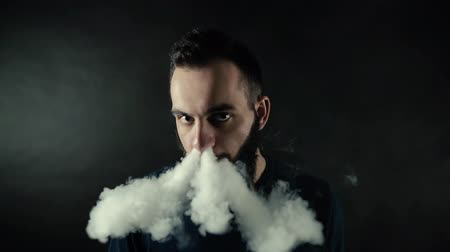 vaper : Close-up portrait of bearded guy exhaling big vapor ring from vape and looks at the camera on black background in slow motion in professional dark studio. Majestic art fog