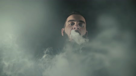 vaper : Close-up portrait of bearded man sending big smoke circle right to camera using two hand on black isolated background in slow motion in professional dark studio. Majestic art fog