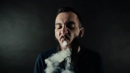 vaper : Close-up portrait of bearded brutal man vaping many small steam circles to camera and looks right into the camera on black background in slow motion in professional dark studio.