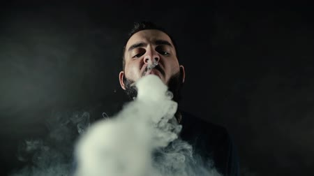 vaper : Close-up portrait of bearded man making many small ring circles of steam with an e-cigarette and looking right into the camera on black isolated background in slow motion in professional dark studio. Stock Footage