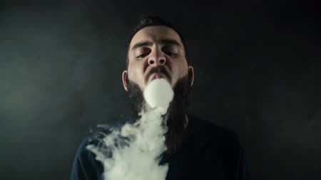 vaper : Close-up portrait of bearded brutal man vaping many small steam circles to camera and looks right into the camera on isolated black background in slow motion in professional dark studio. Stock Footage