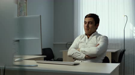 oturum : Man thoughtfully sits in front of monitor in office. Guy puts his hands on his chest and thinks about further actions. Office worker starts typing on the keyboard after brainstorming session.