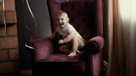 borgonha : Armchair of burgundy color in slow motion. Festive interior with balloons. On face of child is joy
