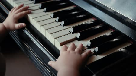 pokus : Little cute baby boy trying to play piano with both hands in slow motion. Child trying to play piano at home. Curious little guy.