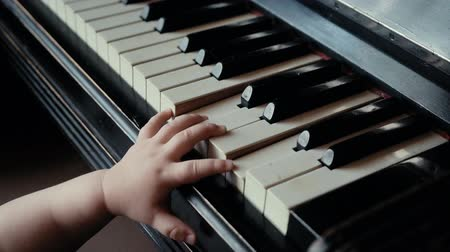 nejistota : Little cute baby boy presses piano keys in slow motion with uncertainty. Child trying to play piano at home. Curious little guy.