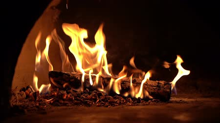 furnace : Fireplace burning in slow motion. Close-up warm cozy burning fire in brick fireplace. Cozy backdrop. Dance of fire on black background Stock Footage
