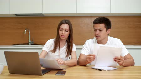 calcular : Young couple managing finances, reviewing their bank accounts using laptop computer in modern bright kitchen. Woman and man doing paperwork together, paying taxes online with notebook Vídeos