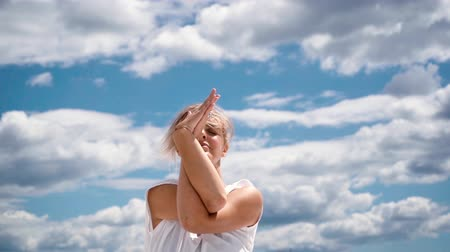 abaixo : Close-up portrait of woman face, girl meditate with hands in Namaste mudra in slow motion in background clouds and blue sky. Camera is shooting face from below. Girl prayer meditating in Namaste mudra Vídeos