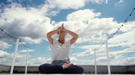 meditál : Portrait of beautiful young woman sitting in lotus pose and putting hands in namaste mudra posture. Girl meditates in background of white clouds and blue sky. Camera shoots from below in slow motion