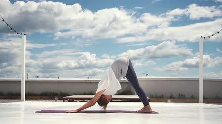 jimnastik : Flexible woman does yoga in slow motion in background of white clouds and bright blue sky. Girl changes yoga pose. Downward facing dog pose - Adho Mukha Svanasana. One Legged Down Dog pose Stok Video