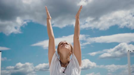 meditál : Close-up portrait of beautiful young woman putting hands in namaste mudra posture. Girl meditates in background of white clouds and blue sky. Camera shoots from below in slow motion