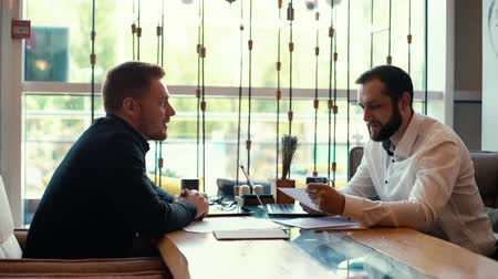 subordinate : Two businessman discusses business project in the interior of the cafe, sitting next to a window. Discussion of planned tasks for break coffee. Subordinate reports to his boss. Shot in slow motion Stock Footage