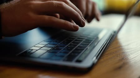 megjegyzés : Close-up of man hands typing on laptop keyboard in slow motion. Man enters password. Closeup man arms carefully writing on laptop computer keyboard
