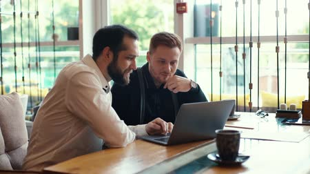meeting negotiate : Portrait of two young business guy sitting at table with laptop near the window in cozy cafe. Shot in slow motion