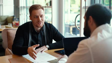 subordinate : Candidate for job presents himself to potential employer in relaxed cafe environment. HR manager having job interview listening with young man in cafe. Subordinate reports to his boss in slow motion Stock Footage
