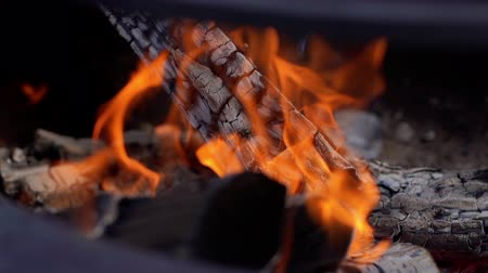 gyúlékony : Burning firewood on the metallic grill on fresh air, close-up. Brazier with burning firewood. Tongues of flame, smoke, coal and ash. Cooking on the barbecue. For outdoors picnic. Shot in slow motion