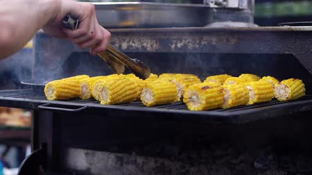mısır koçanı : Cooking corn on grill close-up. Man turns over corn so it doesnt burn on the grill. Shot in slow motion